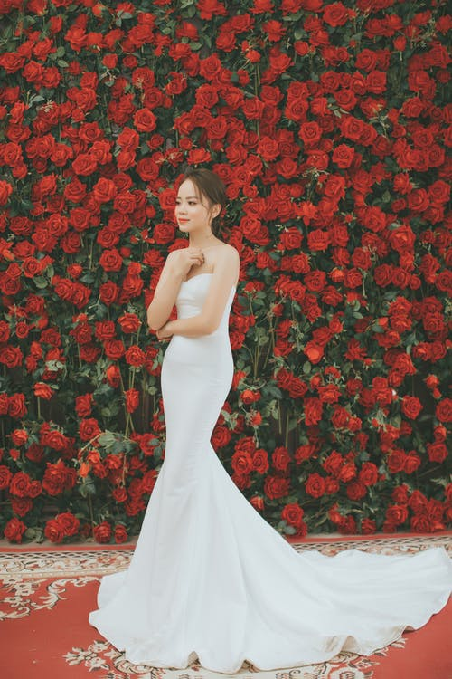 Woman Wearing White Sweetheart Neckline Bodycon Floor Length Wedding Gown Standing and Smiling Near Red Rose Flowers