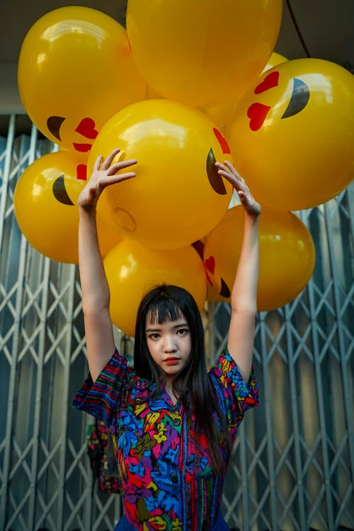Woman Wearing Blue Top Standing in Front of Yellow Balloons