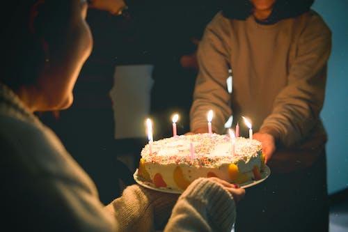Deux Personnes Tenant Un Gâteau Avec Des Bougies Allumées