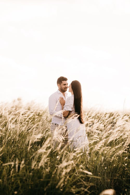 Photography of Man and Woman Standing on Grass Field