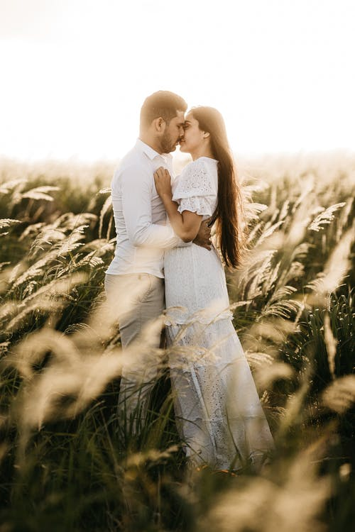 Man and Woman Kissing on Grass Field