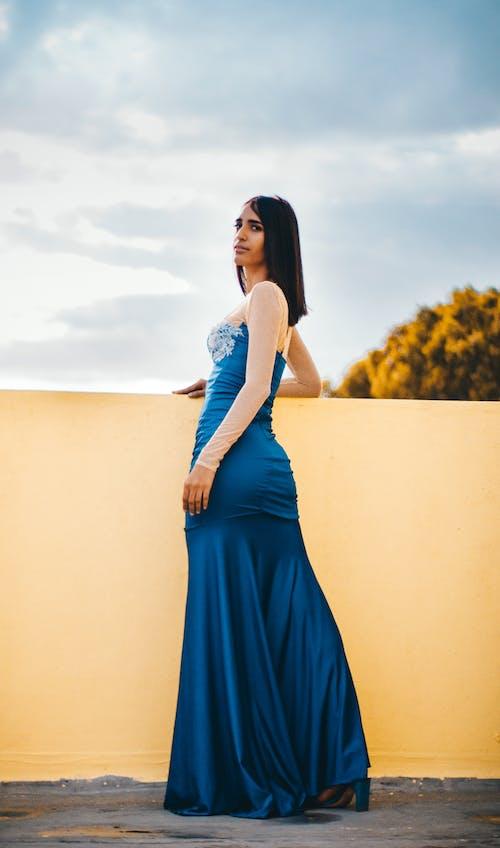 Elegant woman in blur dress standing on terrace