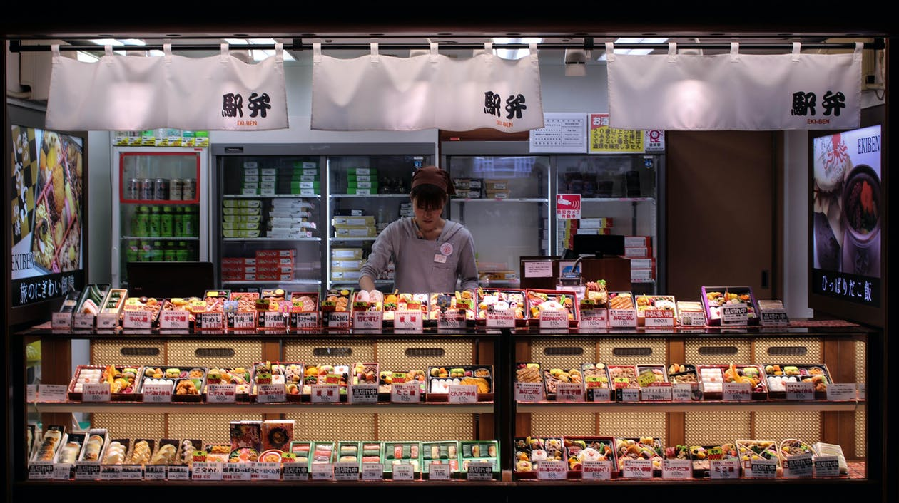 Man in Gray Dress Shirt Standing in Front of Food Display Counter