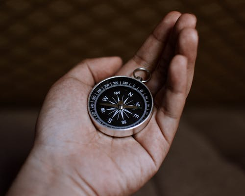 Person Holding a Silver and Black Round Compass