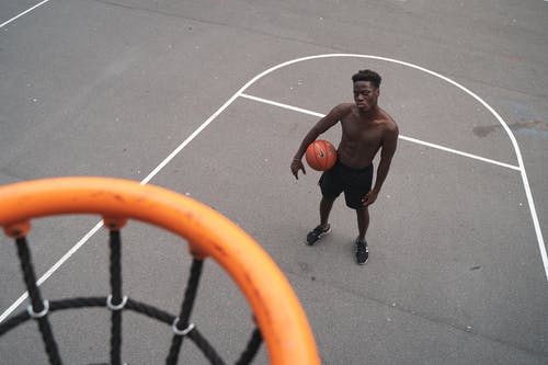 Man Standing Near Basketball Hoop Holding a Basketbal