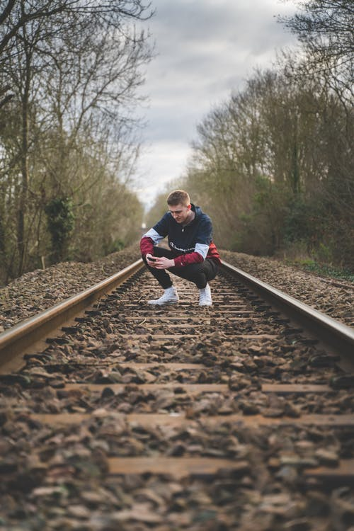Free stock photo of cell phone, champion, crouching, male