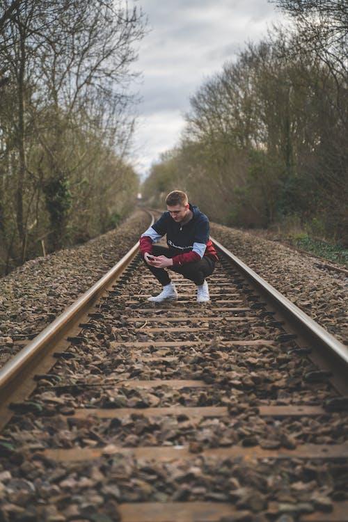 Man Crouching on Train Rails
