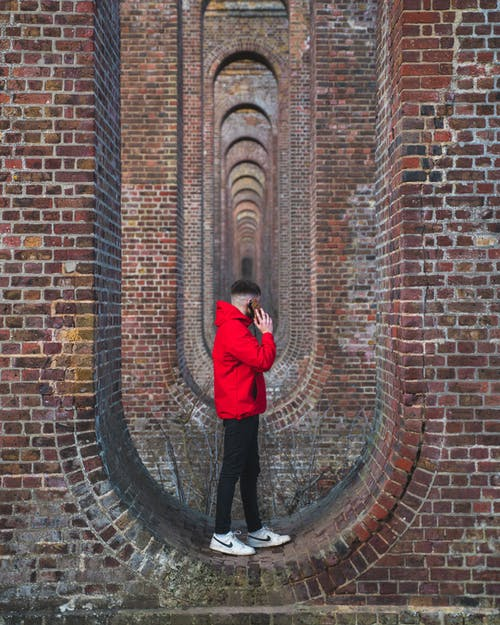 Man in Red Jacket and Black Pants Standing on Red Brick Wall