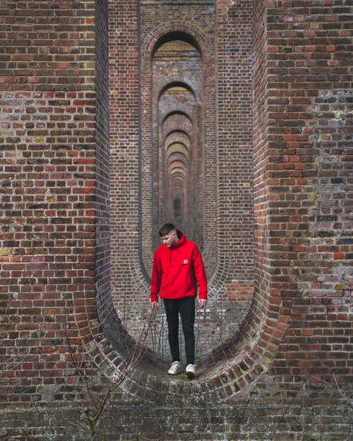Man in Red Jacket Standing on Brick Wall