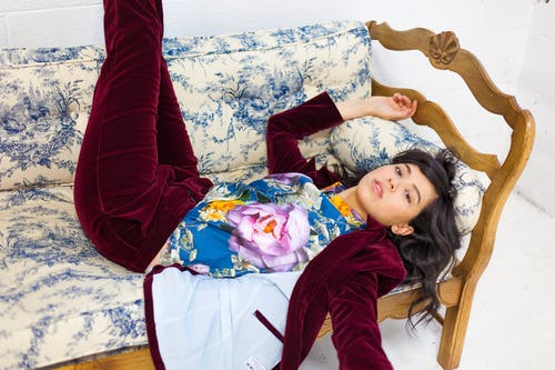 Woman Wearing Floral Top While Lying on Sofa