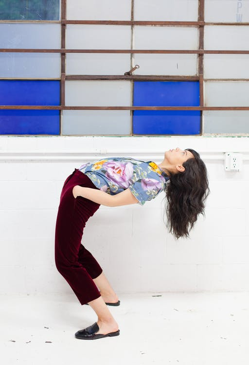 Woman in Red Pants and Blue and White Floral Shirt Leaning Backward