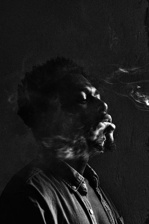 Monochrome Photo Of Man Releasing Smoke