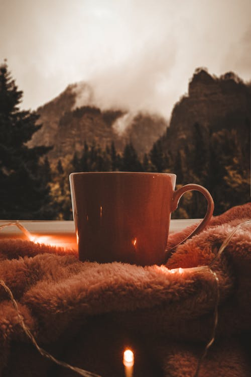 Cozy plaid with mug of warming beverage in garland lights with view of misty mountains