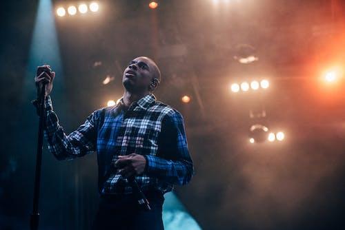 Homme Tenant Un Microphone Sur Scène