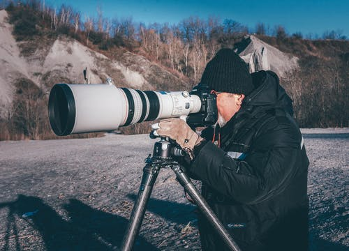 Man Taking Picture Using a Camera With Telephoto Lens