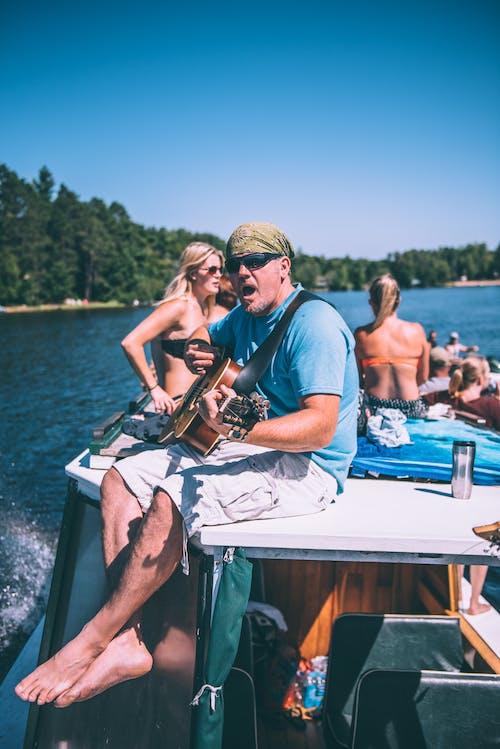 Kostnadsfri bild av artist, båt, dagtid, gitarr