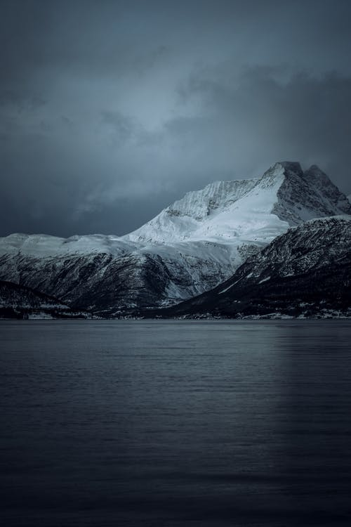 Snow-covered Mountain Facing Body of Water Under Heavy Clouds