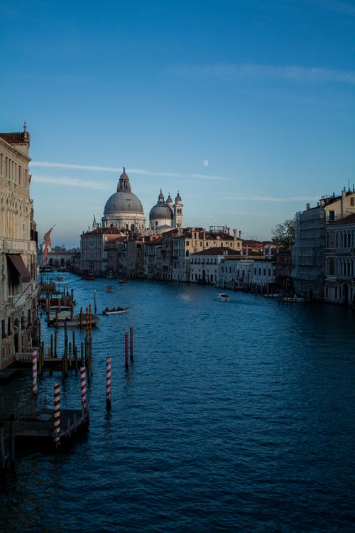 Blue canal water flowing among old city buildings and domed church located in Venice