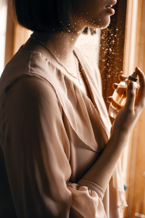 Crop sensual woman spraying perfume