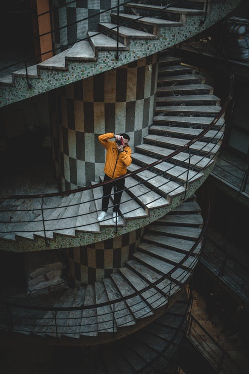 Man in Yellow Jacket and Black Pants Standing on Stairs