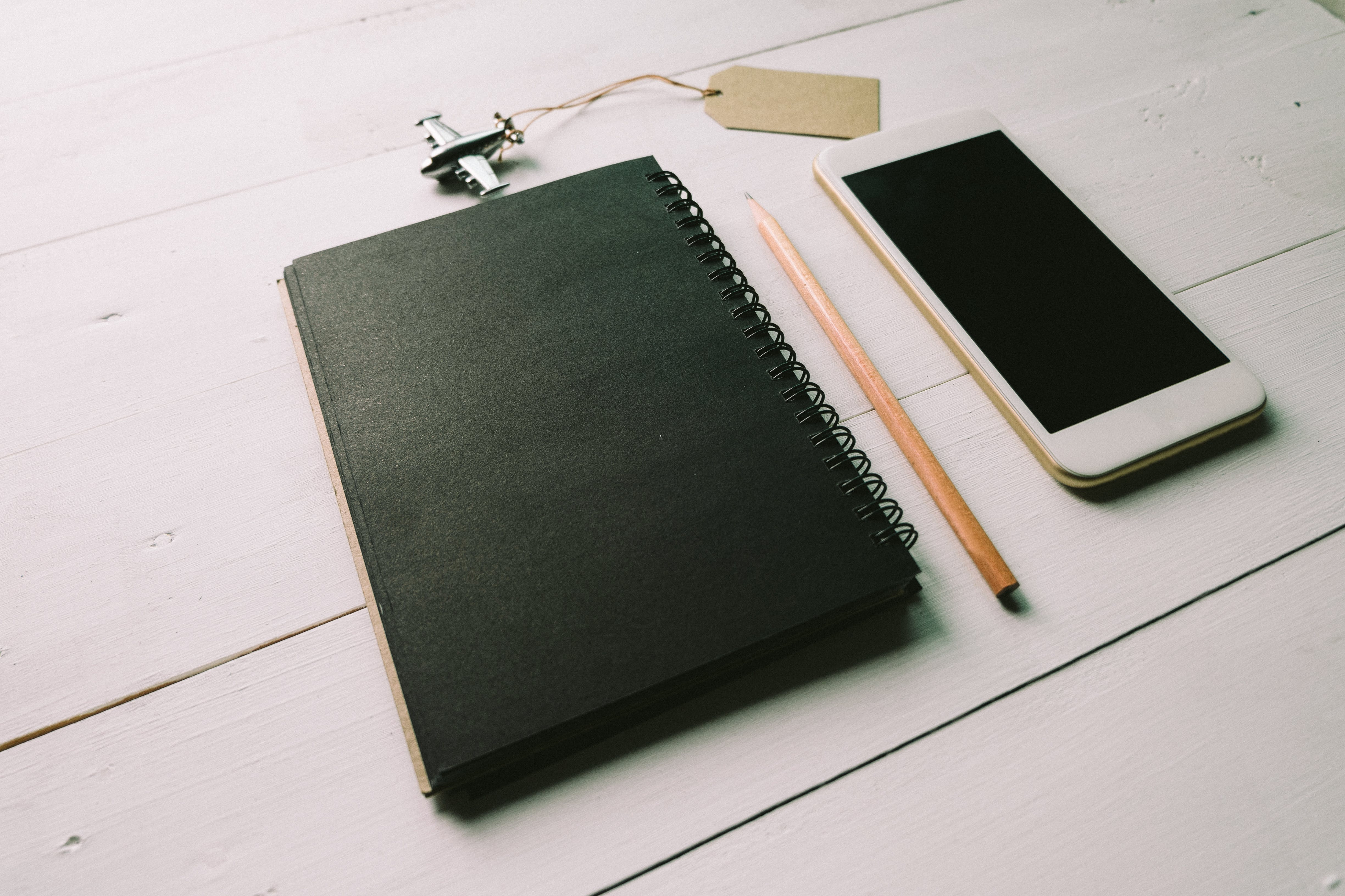 Flatlay Photo of Black Spiral Book Near Brown Pencil and White Smartphone
