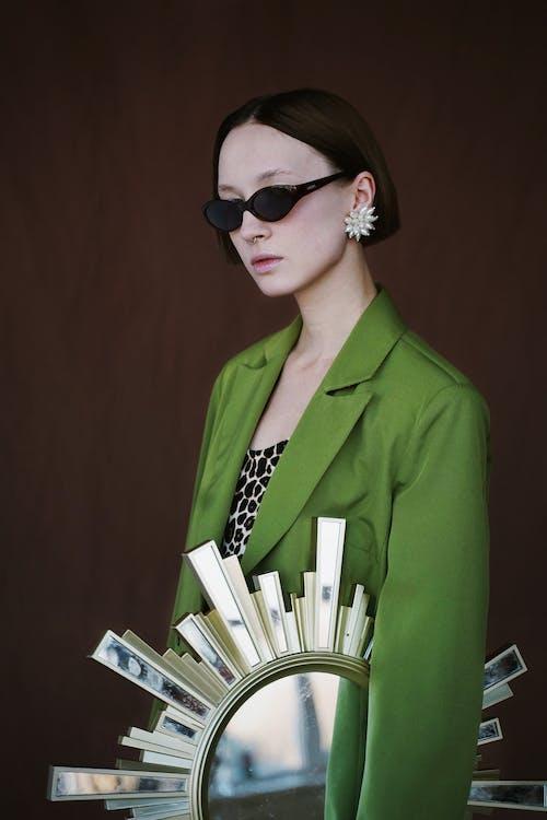 Woman Wearing Sunglasses and Green Blazer While Holding Sunburst Wall Mirror