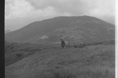 grey scale photo of a man walking towards a hill