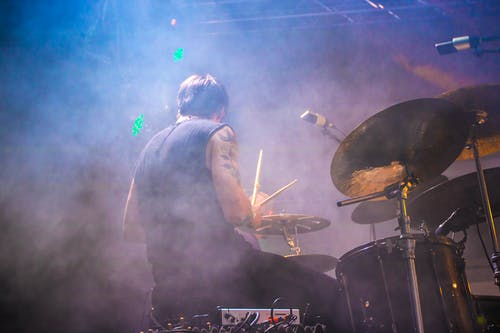 Performing Drummer Surrounded by Fogs