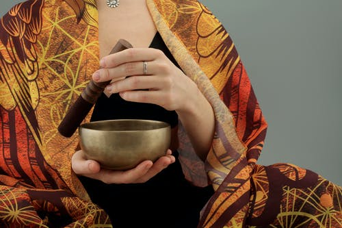 Woman Holding a Wooden Stick and a Bronze Bowl