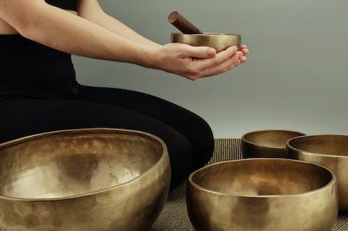 Woman Sitting on Rug Near Brass Bowls
