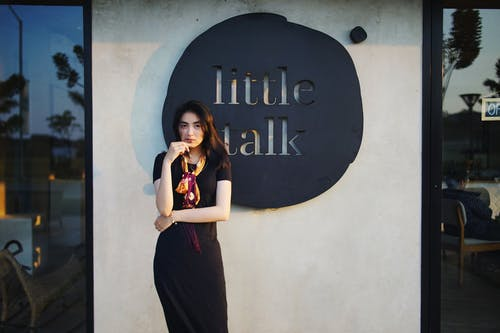 Woman in Black Dress Standing Beside Wall