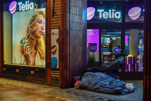 Person Sleeping In Pavement Near Glass Window