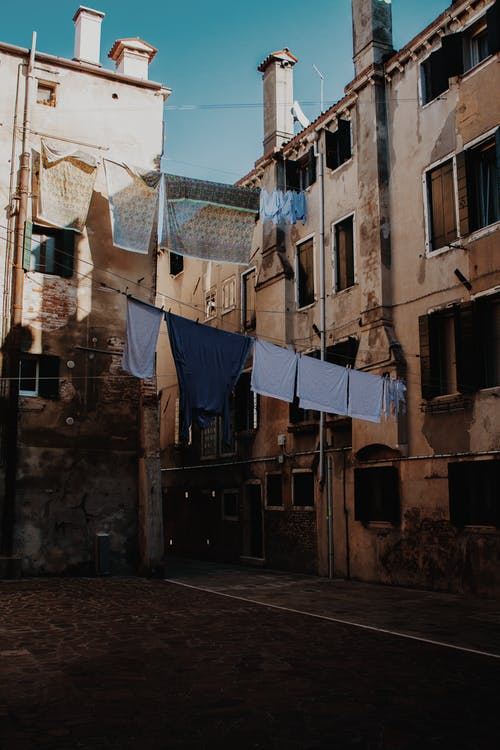 Narrow street with shabby walls of aged apartment buildings with clothes drying on ropes