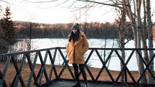 Woman in Brown Coat Standing on Wooden Deck
