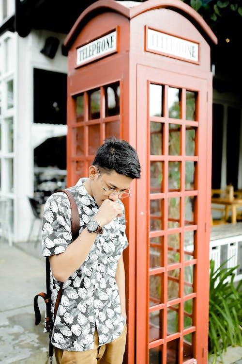 Stylish pensive guy near phone booth