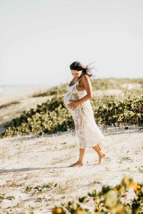 Pregnant Woman in White Dress Walking on Beach