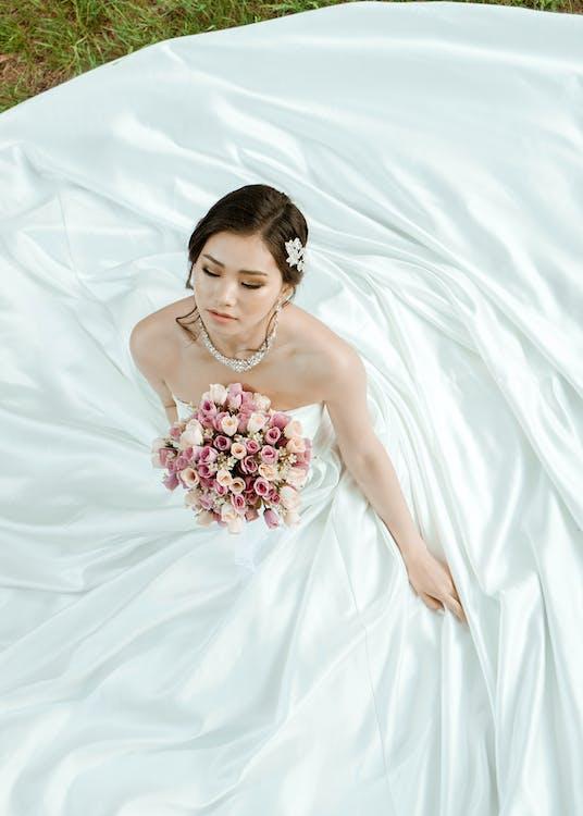 Woman in White Wedding Dress Sitting on Grass