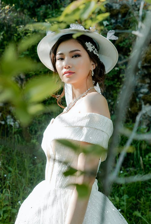 Woman Wearing White Tube Dress and White Hat Near Plants
