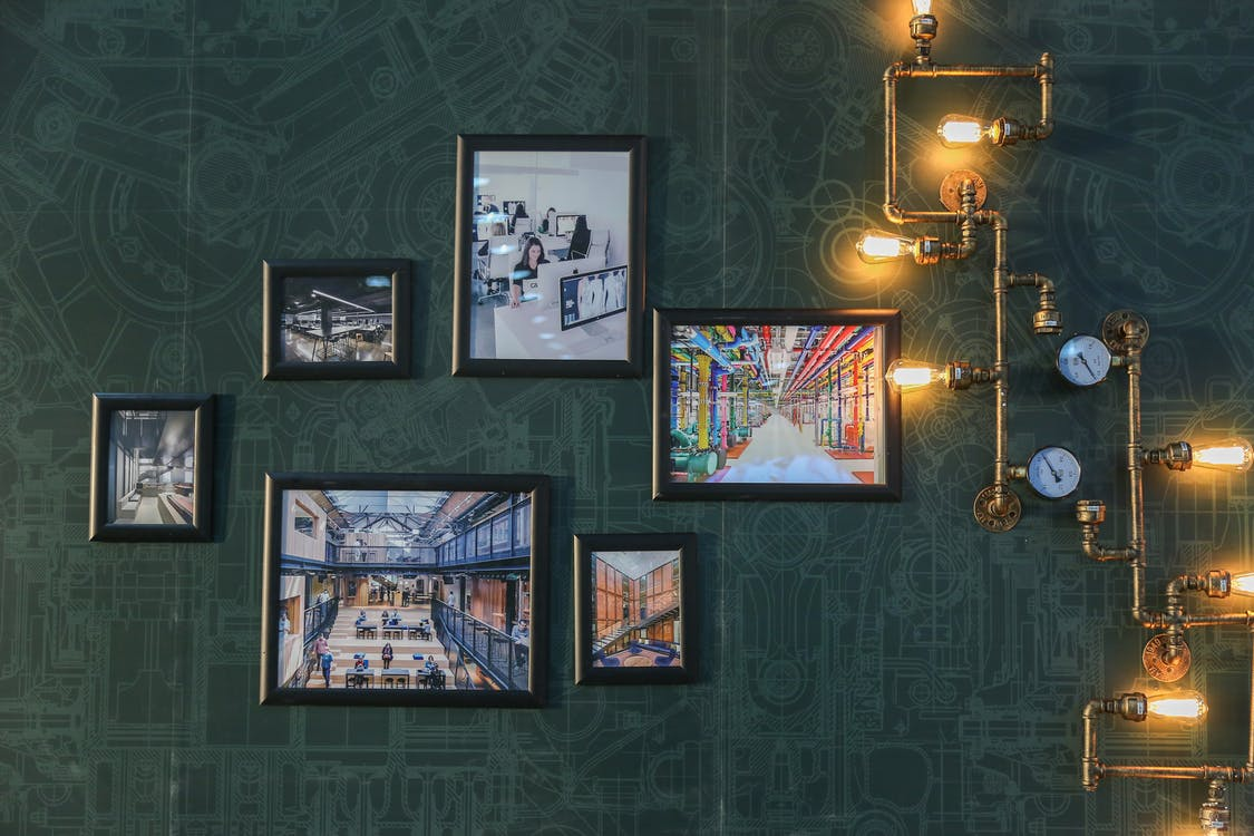Assorted Paintings on Green Wall