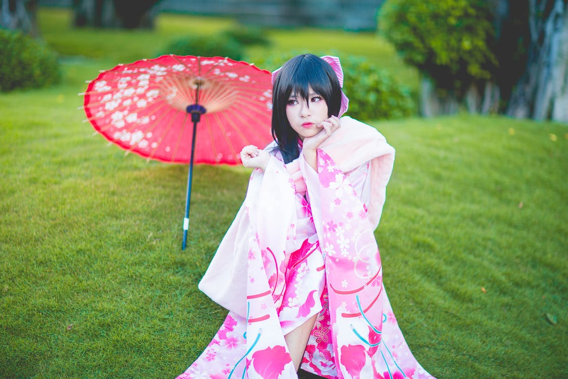 Woman Wearing Pink and White Floral Dress With Red Umbrella