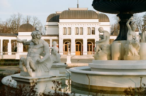 Exterior of park with statues around fountain located near white building at daytime