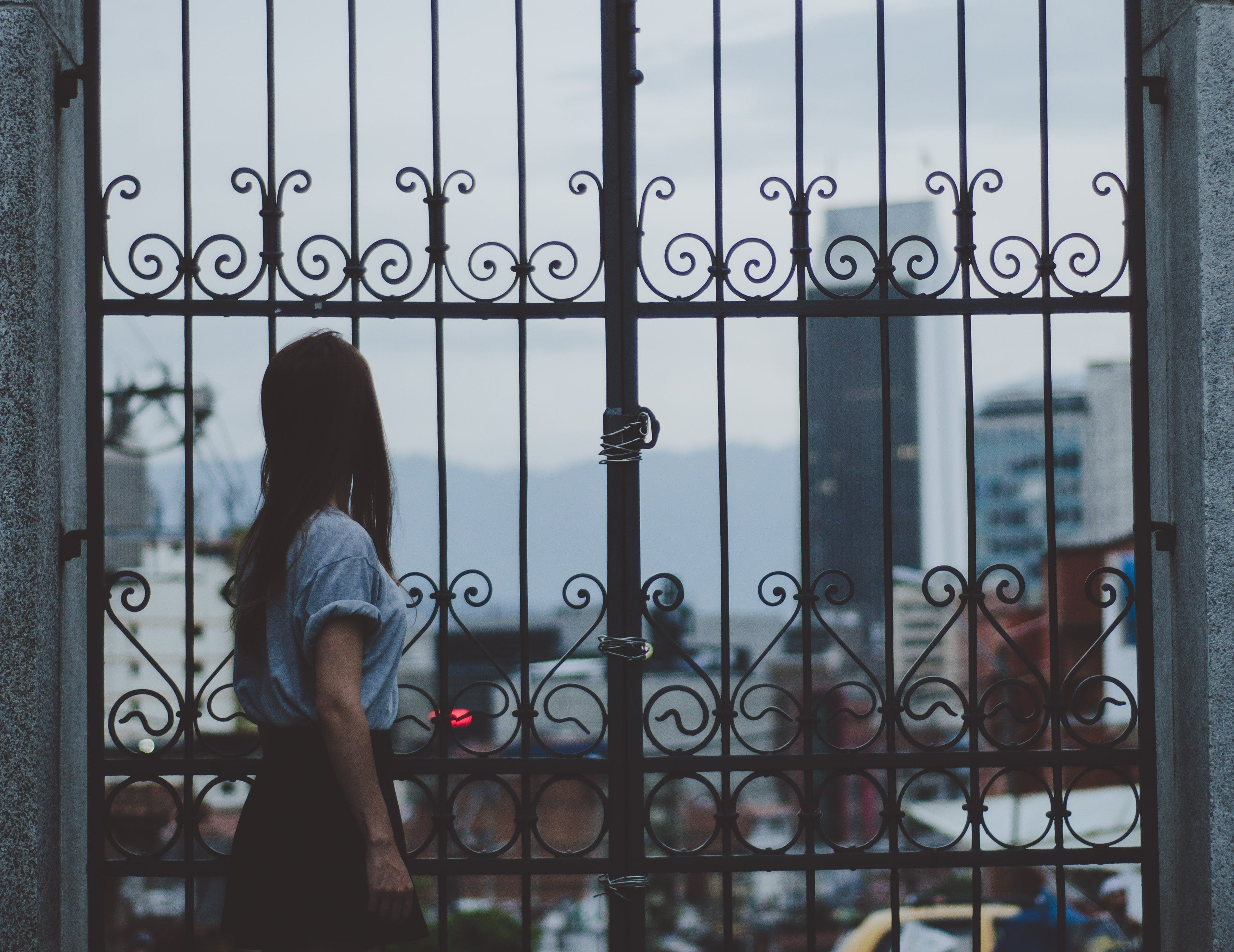 Woman Standing Beside Gate
