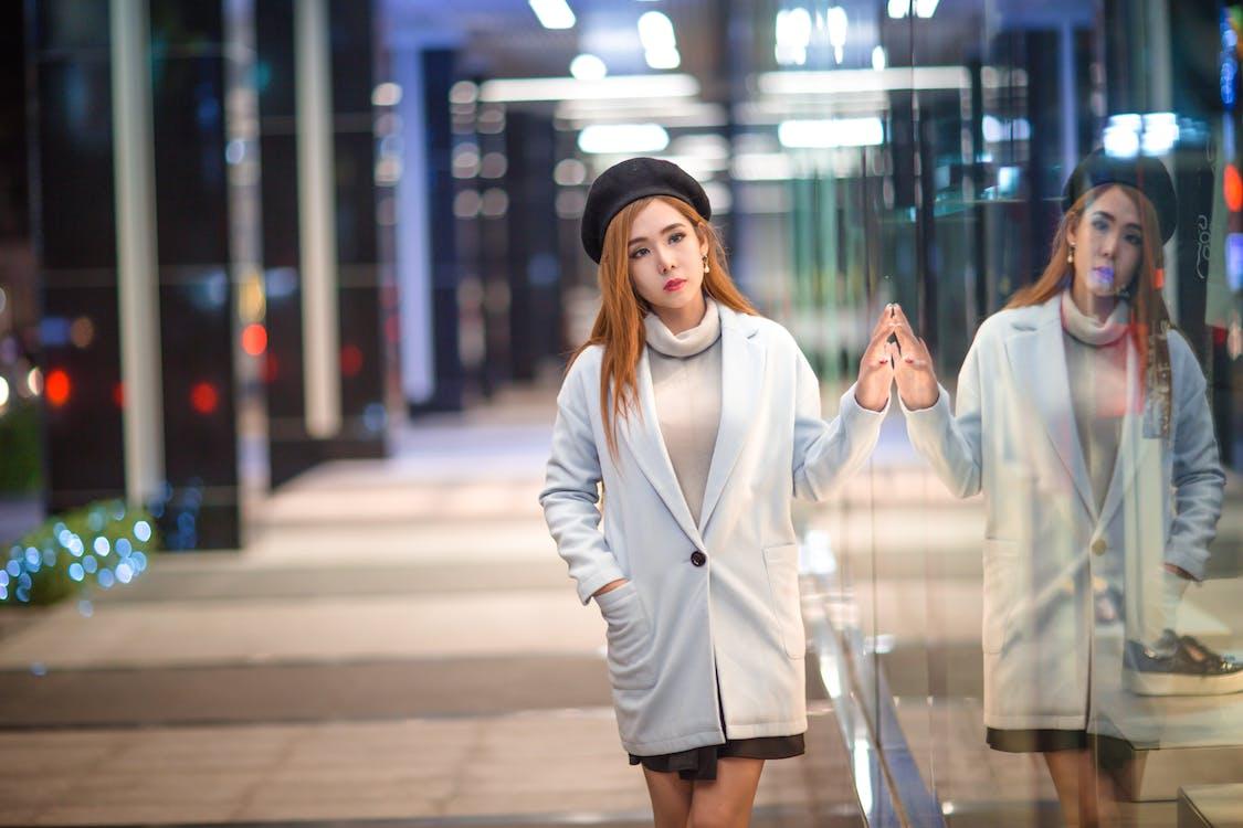 Woman Wearing Jacket Standing Beside Glass Wall