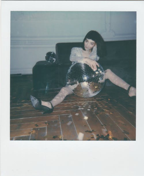 Woman Sits on the Floor With Disco Ball