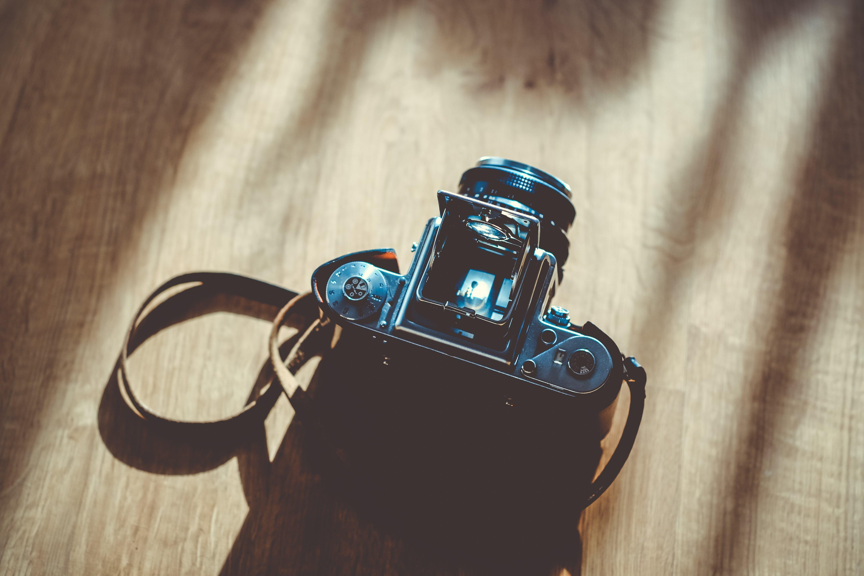 Black Dslr Camera on Brown Surface