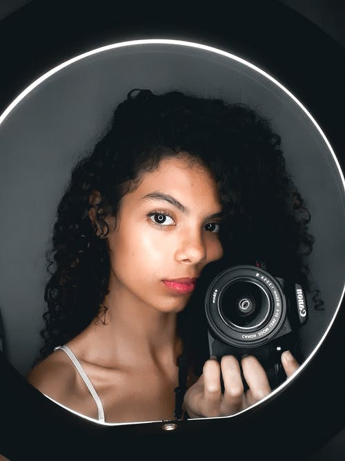 женщина держит черную камеру Canon Dslr
