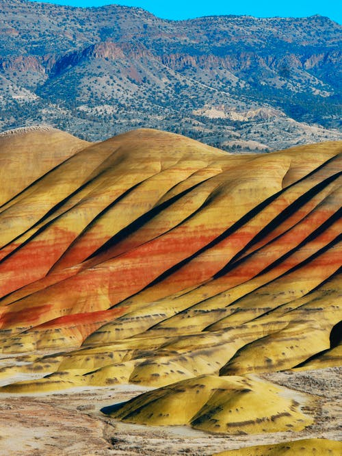 Picturesque view of high hills of badlands without vegetation exposed to water and wind erosion in Painted Hills National Monument