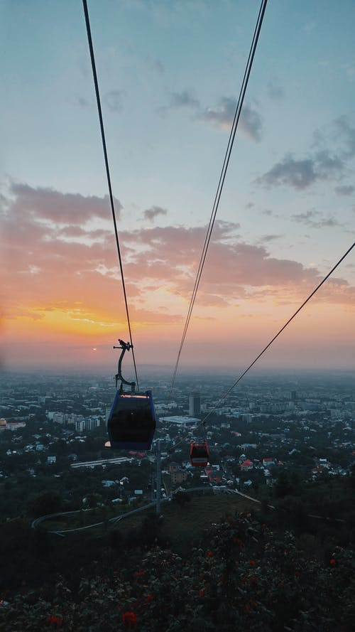 Cableway above city during bright sunset