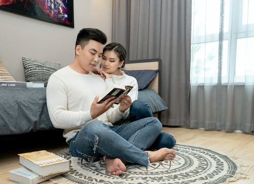 Man and Woman Sitting on Floor Reading Book Indoors