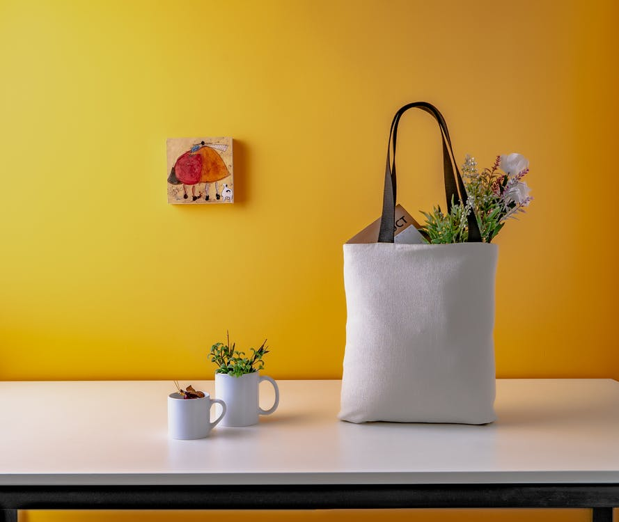 Two White Ceramic Mugs and a white bag on Wooden Table